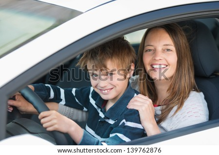 Beautiful mother teaching her son how to drive a car