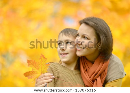 beautiful mother with a boy on a walk during the fall of the leaves in the park