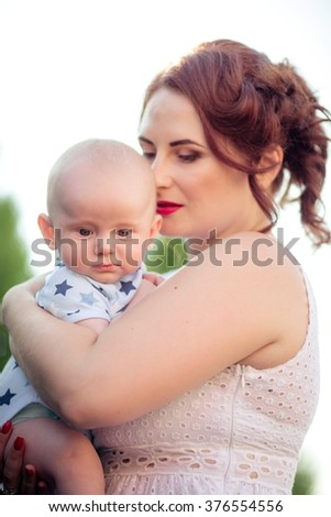 Beautiful mother with baby boy on spring garden
