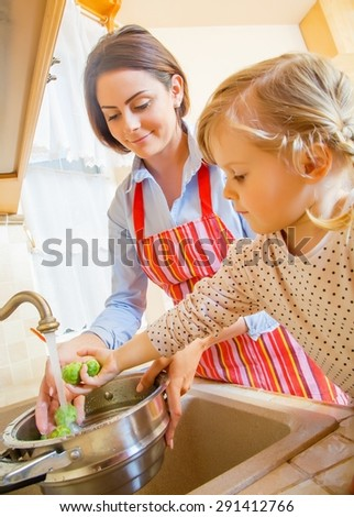 Beautiful mother with cute little daughter preparing food in the kitchen.