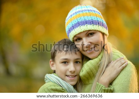 Beautiful mother with her son on a walk during the fall of the leaves in the park - stock photo