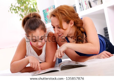 Beautiful mother with her teenager daughter have fun at home