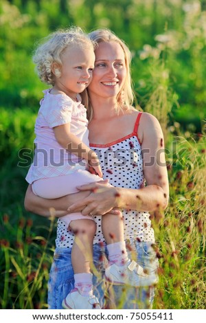 Beautiful mother with infant curly-headed blond daughter on meadow in sunset sun beams