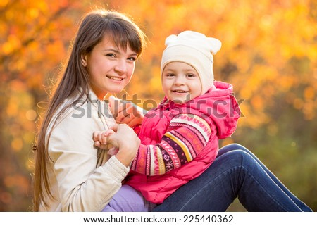 beautiful mother with kid girl outdoors in fall - stock photo