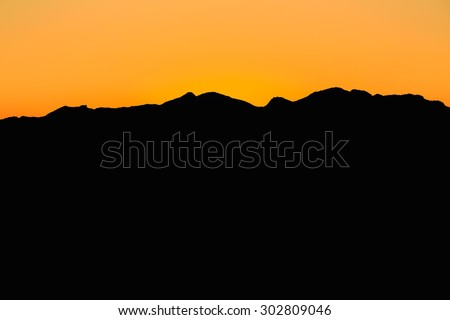Beautiful Mountain And Sunset at Mijas, Spain. Dark Silhouette of Mountains on Yellow Sunrise Background - stock photo