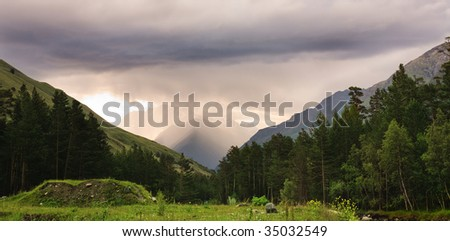 Beautiful mountain cloudy landscape with green grass
