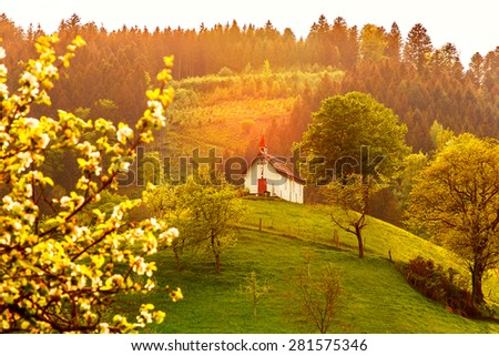 Beautiful mountain forest landscape with church at sunset. Germany, Black Forest, Simonswald. - stock photo