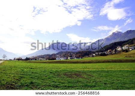 Beautiful mountain landscape in the Alps with a village in the background at sunrise, Tirol, Austria - stock photo