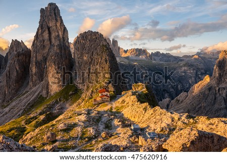 beautiful mountain landscape in the Dolomites at sunset, desolate rocks with a small house