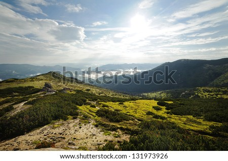 Beautiful mountain landscape. Mountains are visible to the horizon. Cloudy sky with the sun. There is a fog in the valley. The hills covered with grass and forest. No one is around. - stock photo