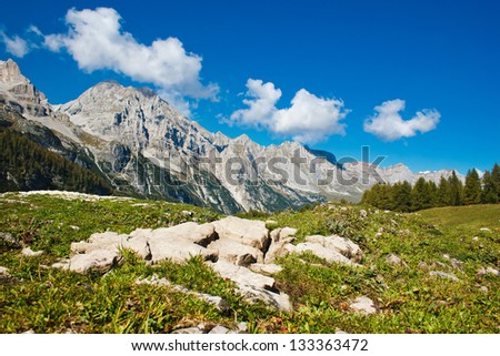 Beautiful mountain landscape. There are big stones in the foreground. Ridge goes over the horizon. There is a forest at the foot of the mountains. The sky is blue and cloud.  Nobody is around.