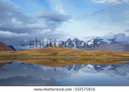 Beautiful mountain landscape with lake surface reflecting the sky above. Europe, Georgia, Upper Svaneti, Major Caucasus ridge, Koruldi Lake near Mestia. - stock photo