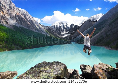Beautiful mountain landscape with the lake and the jumping man. Sports extreme. - stock photo