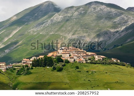 Beautiful mountain landscape with view on the village of Castelluccio, Umbria, Italy, well known for their world famous lentils fields. - stock photo