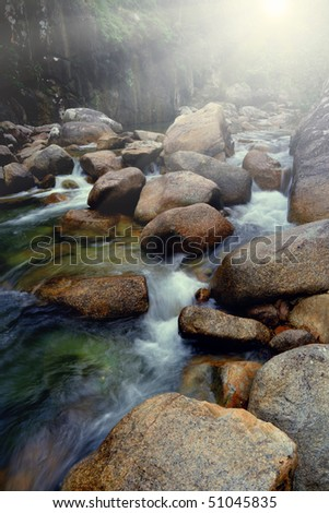 Beautiful Mountain River with Blurred Water in the Sunlight - stock photo