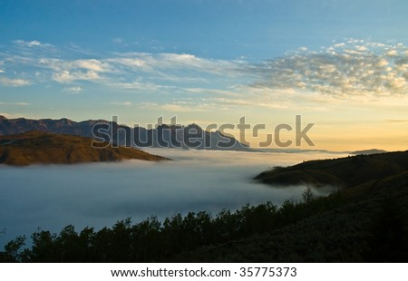 Beautiful mountain sunrise at daybreak with fog bank in the valley below. Skyline is filled with fluffy clouds. - stock photo