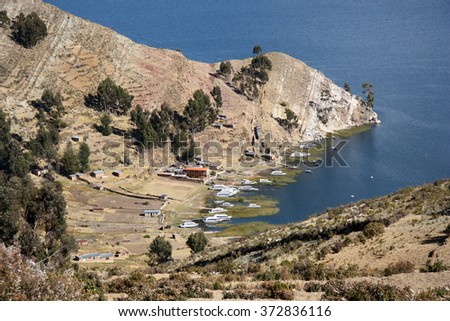 Beautiful mountain view with boats in a bay on Isla del Sol on Lake Titicaca, Bolivia - stock photo