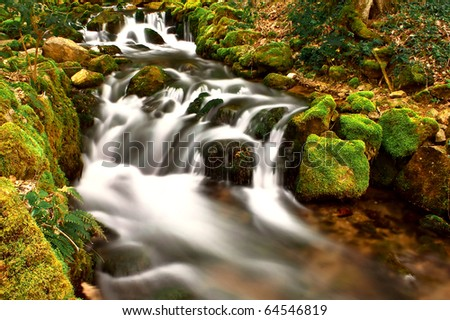 Beautiful mountain waterfall with river - stock photo