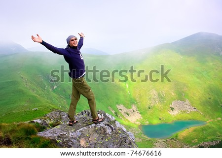 Beautiful mountains landscape with lake  in Carpathian mountains and man on the top - stock photo