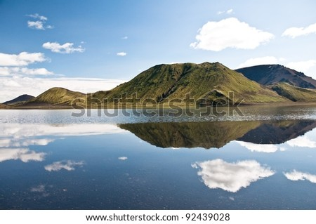 beautiful mountains reflectng in the lake, clouds - stock photo