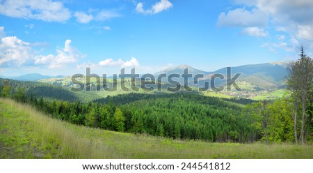 Beautiful mountainside panorama quiet plateau in Ukrainian Carpathians. White cumulus clouds in bright blue heaven above towns in the lowland and high hills overgrown with green firry groves - stock photo