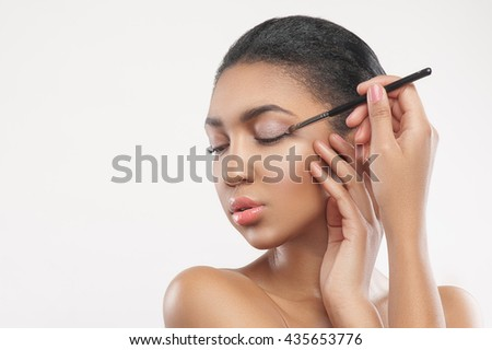 Beautiful mulatto girl is doing pretty make-up - stock photo