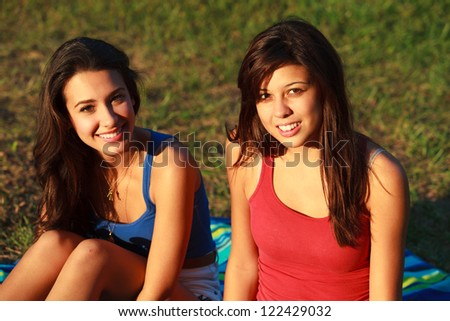 Beautiful multicultural young college women enjoying outdoor campus life. - stock photo