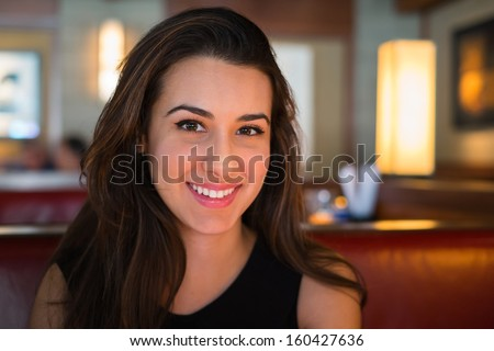 Beautiful multicultural young woman portrait in a restaurant setting. - stock photo
