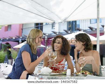 Beautiful multiethnic female friends enjoying wine at outdoor cafe - stock photo