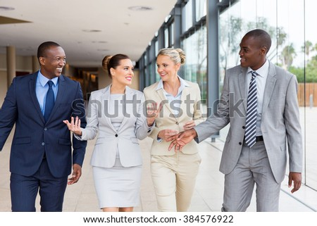 beautiful multiracial businesspeople walking together in office building - stock photo