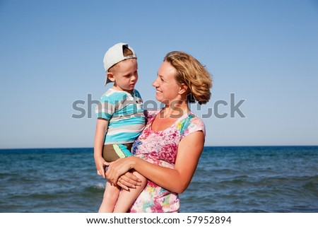 Beautiful mum holds the son on hands and looks at it on seacoast - stock photo