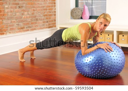 Beautiful muscular blond woman wearing athletic clothing doing plank abdomen exercise with Pilates equipment ball at home exercise studio.