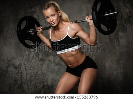 Beautiful muscular bodybuilder doing exercise with weights - stock photo
