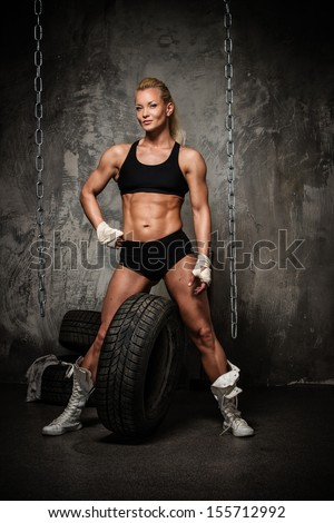 Beautiful muscular bodybuilder woman posing against tyres and chains  - stock photo
