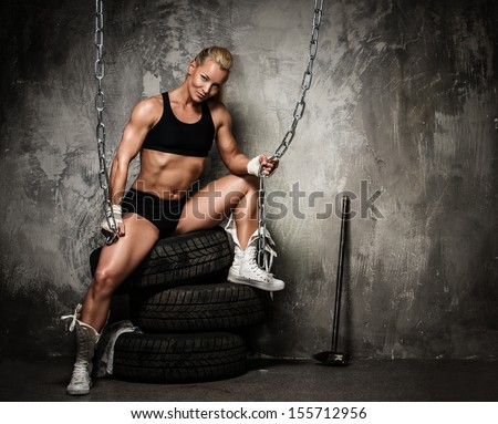 Beautiful muscular bodybuilder woman sitting on tyres and holding chains  - stock photo