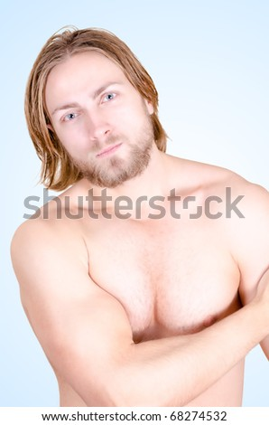 Beautiful muscular male model in light blue background - stock photo