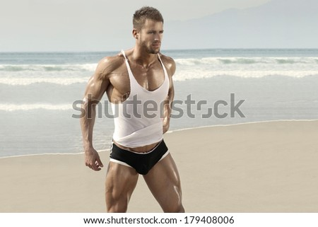 Beautiful muscular man on perfect beach in warm summer light - stock photo