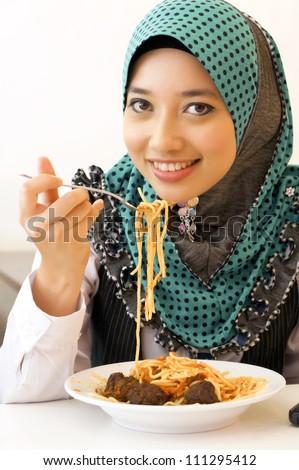 Beautiful Muslim eating Spaghetti - stock photo