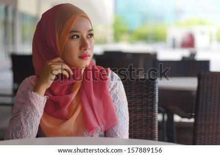 Beautiful Muslim girl at the cafe - stock photo