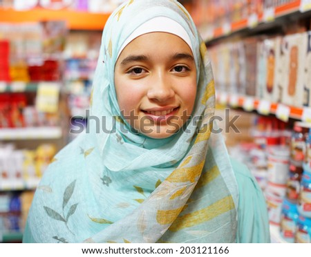Beautiful Muslim girl posing with hijab and smiling - stock photo