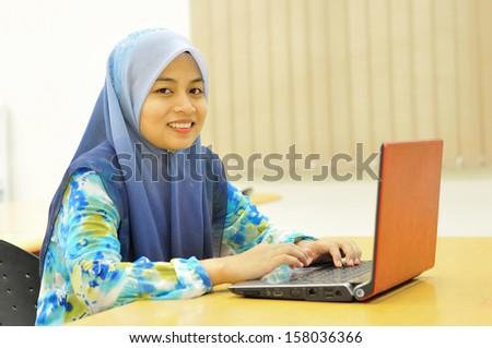 Beautiful muslim girl with laptop,  sellective DOF - stock photo