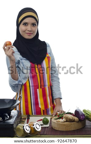 Beautiful muslim woman holding tomato and prepare for cooking healthy food in the kitchen