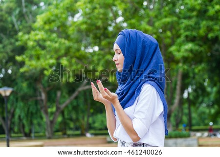 beautiful muslim woman in blue hijab standing praying on green tree background by show her hand up and close her eye.