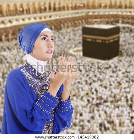 Beautiful muslim woman praying at Kaaba, Mecca, Saudi Arabia - stock photo