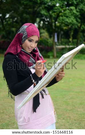 Beautiful muslim woman wearing scarf with white paper painting