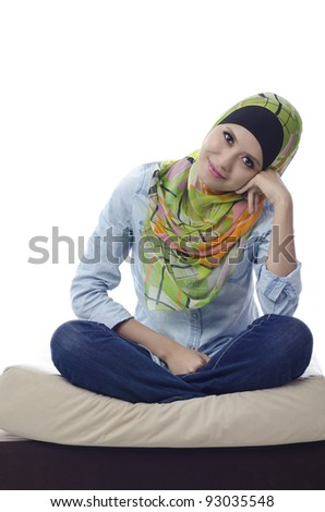beautiful muslim woman with stylish head scarf sitting with cross-legged on a couch - stock photo