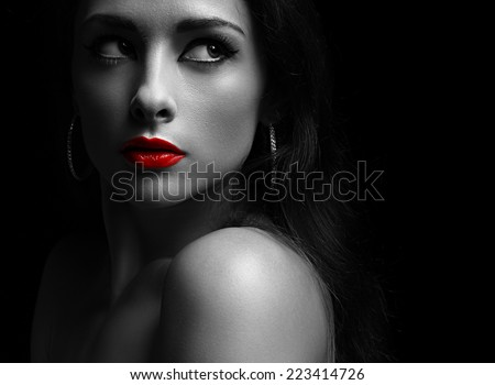 Beautiful mysterious woman in darkness looking dramatic with red lips. Closeup portrait on black background - stock photo