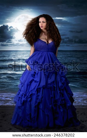 Beautiful Mysterious woman in long blue dress at ocean beach. Fantasy woman. Water Goddess. Book cover. - stock photo