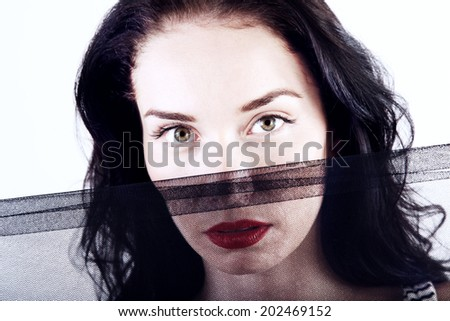 Beautiful mysterious young woman hiding behind dark veil