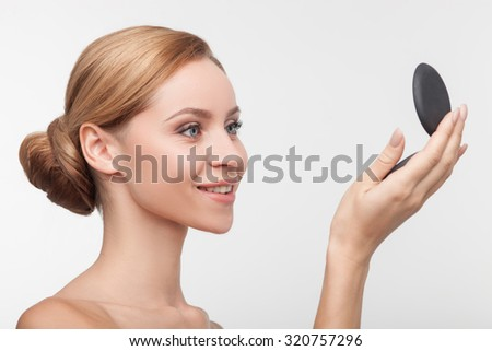 Beautiful naked girl is standing and holding a mirror. She is looking at it and smiling. Her skin is perfect. Isolated on background - stock photo